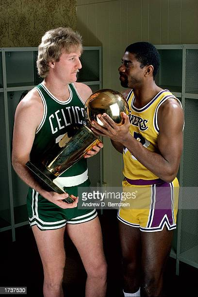 Larry Bird of the Boston Celtics poses for a portrait with Magic Johnson of the Los Angeles Lakers with each holding the NBA Championship Trophy at...