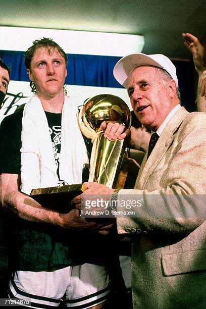 Larry Bird of the Boston Celtics poses with General Manager Red Auerbach after winning the 1986 NBA Championship by defeating the Houston Rockets in...