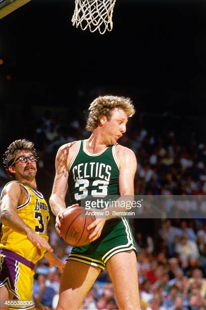 Larry Bird of the Boston Celtics rebounds the ball during a game against Kurt Rambis of the Los Angeles Lakers in 1984 at the Great Western Forum in...
