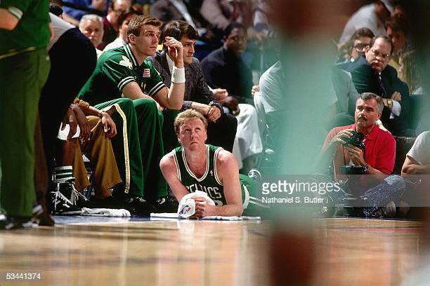 Larry Bird of the Boston Celtics rests on the floor near the bench area during the NBA game against the New York Knicks at the Madison Square Garden...