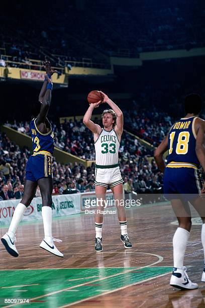 Larry Bird of the Boston Celtics shoots a jump shot against Larry Smith of the Golden State Warriors during a game played in 1984 at the Boston...