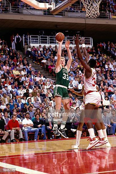 Larry Bird of the Boston Celtics shoots a jump shot during a 1990 NBA game against Hakeem Olajuwon of the Houston Rockets at the Summit in Houston...
