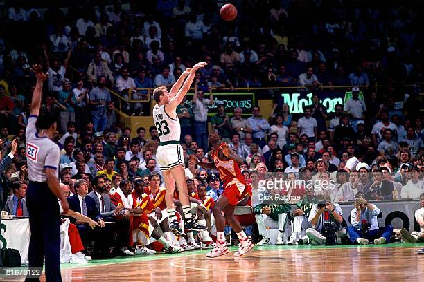 Larry Bird of the Boston Celtics shoots a jump shot over Dominique Wilkins of the Atlanta Hawks circa 1990 at the Boston Garden in Boston...