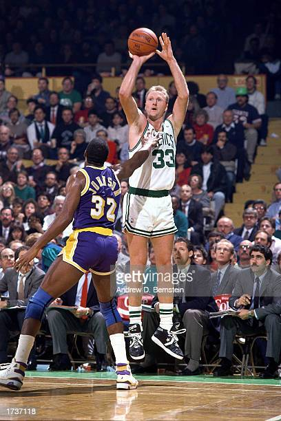 Larry Bird of the Boston Celtics shoots a jump shot over Magic Johnson of the Los Angeles Lakers during the 1989 NBA game at The Boston Garden in...