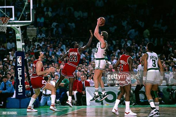 Larry Bird of the Boston Celtics shoots a jumper against Michael Jordan of the Chicago Bulls during an NBA game played in 1987 at the Boston Garden...