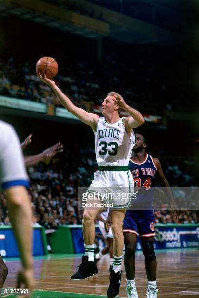 Larry Bird of the Boston Celtics shoots a layup against Charles Oakley of the New York Knicks during a game circa 1991 at the Boston Garden in Boston...