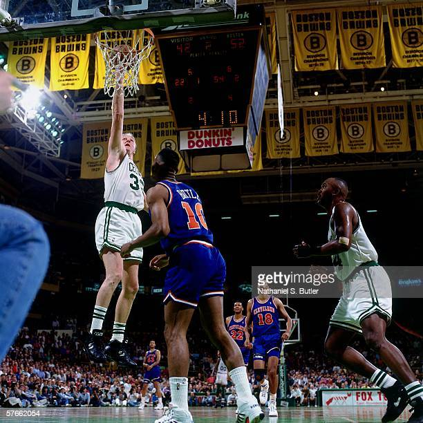 Larry Bird of the Boston Celtics shoots a layup against John Battle of the Cleveland Cavaliers during a game circa 1992 at the Boston Garden in...
