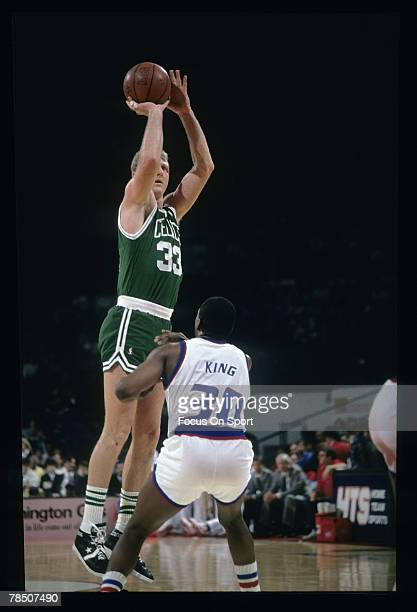 Larry Bird of the Boston Celtics shoots a long jumper over Bernard King of the Washington Bullets during a circa 1990 NBA basketball game at the...
