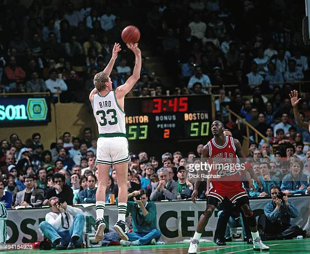 Larry Bird of the Boston Celtics shoots against Michael Jordan of the Chicago Bulls during a game played circa 1990 at the Boston Garden in Boston,...