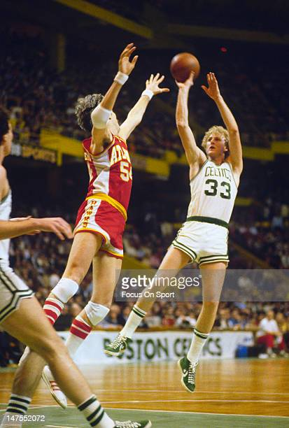 Larry Bird of the Boston Celtics shoots over Mark Landsberger of the Atlanta Hawks during an NBA basketball game circa 1984 at The Boston Garden in...