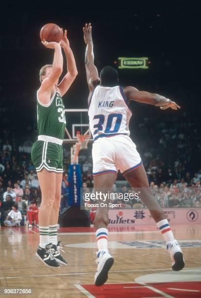 Larry Bird of the Boston Celtics shoots shoots over Bernard King of the Washington Bullets during an NBA basketball game circa 1990 at the Capital...