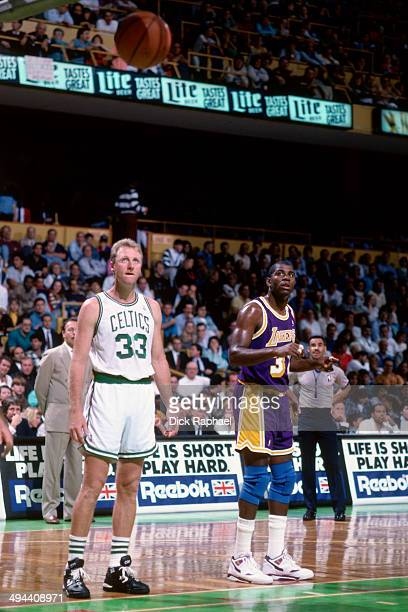 Larry Bird of the Boston Celtics stands on the court during a game against Magic Johnson of the Los Angeles Lakers circa 1992 at the Boston Garden in...