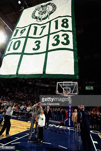Larry Bird of the Boston Celtics stands on the court with his son as they watch his number 33 raised to the rafters along the retired numbers prior...