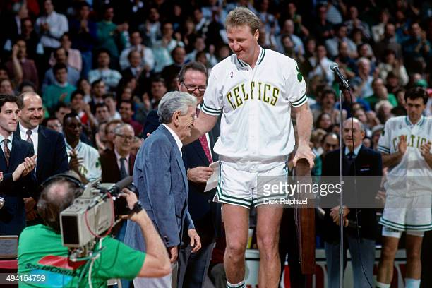 Larry Bird of the Boston Celtics stands on the court with NBA announcer Johnny Most during a game played circa 1990 at the Boston Garden in Boston...