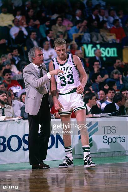 Larry Bird of the Boston Celtics talks with head coach Jimmy Rodgers during a game played in 1987 at the Boston Garden in Boston Massachusetts NOTE...