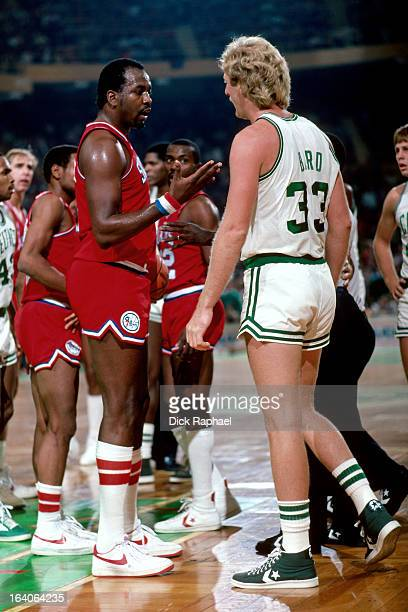 Larry Bird of the Boston Celtics talks with Moses Malone of the Philadelphia 76ers during a game played circa 1983 at the Boston Garden in Boston...