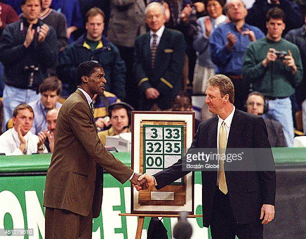 Larry Bird presents Robert Parish with a framed miniature banner with his retired number 00