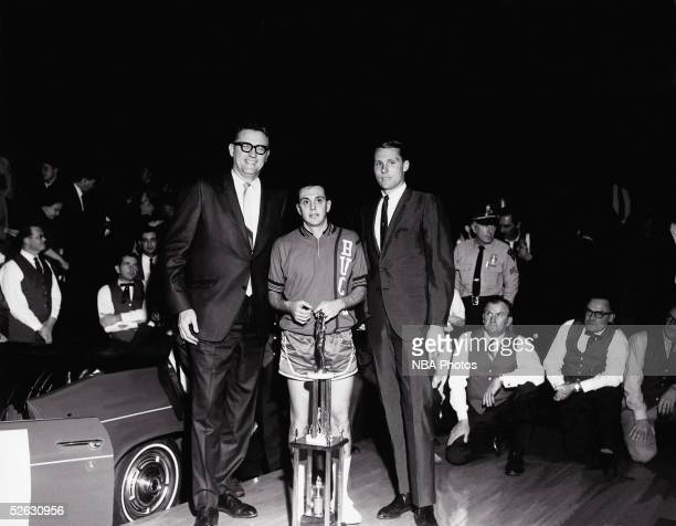 Larry Brown of the New Orleans Buccaneers receives the MVP trophy circa 1968 with George Mikan on his left and Rick Barry on his right after the...