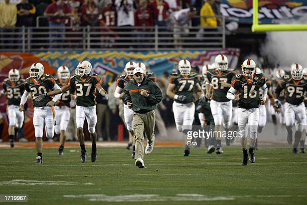 Larry Coker head coach of the Miami Hurricanes takes the field with his team during the Tostitos Fiesta Bowl game against the Ohio State Buckeyes at...