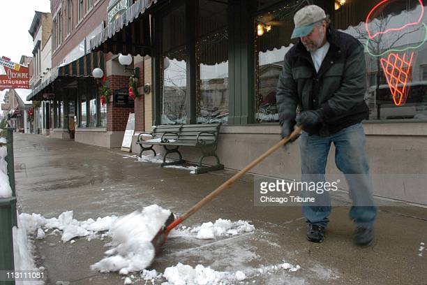 Larry Cook clears snow December 15 in Lake Geneva Wisconsin an area that some say is less likely to see a disastrous real estate bust