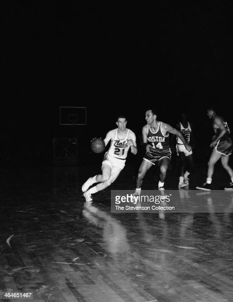 Larry Costello of the Syracuse Nationals dribbles the ball against Bob Cousy of the Boston Celtics during a game played circa 1962 at the Onondaga...