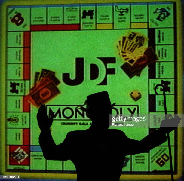 Larry Cripe suited up as 'Mr Money Bags' is silhouetted against a projected Monopoly board as he greets dinner guests at the Juvenile Diabetes...