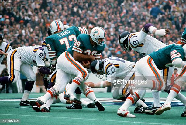 Larry Csonka of the Miami Dolphins carries the ball and gets hit by Roy Winston of the Minnesota Vikings during Super Bowl VIII at Rice Stadium...