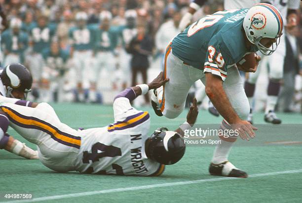 Larry Csonka of the Miami Dolphins runs through the tackle of Nate Wright of the Minnesota Vikings during Super Bowl VIII at Rice Stadium January 13...