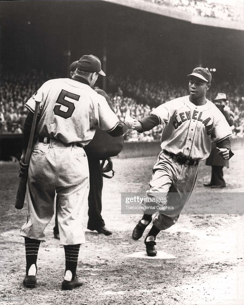 BOSTON - MAY 10, 1948. Larry Doby has just homered and Cleveland Indians manager and shortstop Lou Boudreau welcomes him home during a game at Fenway Park in Boston on May 10, 1948.