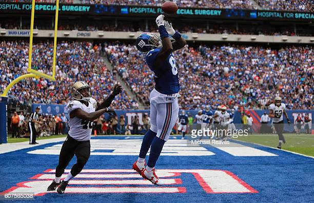 Larry Donnell of the New York Giants attempts to catch the ball against Vonn Bell of the New Orleans Saints during the first quarter at MetLife...