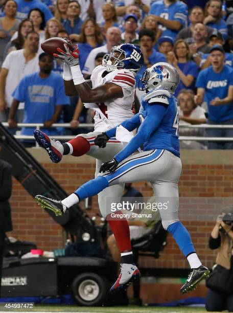 Larry Donnell of the New York Giants catches a second quarter touchdown next to Isa AbdulQuddus of the Detroit Lions at Ford Field on September 8...