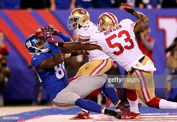 Larry Donnell of the New York Giants makes the catch for the game winning touchdown as NaVorro Bowman and Antoine Bethea of the San Francisco 49ers...