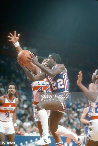 Larry Drew of the Kansas City Kings looks to get his shot off over Rick Mahorn of the Washington Bullets during an NBA basketball game circa 1984 at...