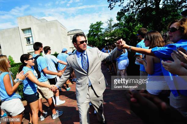 Larry Fedora firstyear coach of the North Carolina Tar Heels shakes hands during the Old Well Walk before a game against the Elon Phoenix at Kenan...