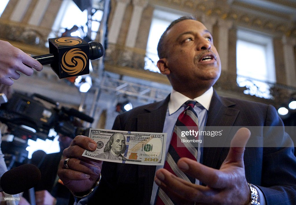 Larry Felix, director of the Bureau of Engraving and Printing, speaks to the media while holding the new $100 bill at its unveiling at the Treasury in Washington, D.C., U.S., on Wednesday, April 21, 2010. Complete with advanced technology to combat counterfeiting, the new design for the $100 note retains the traditional look of U.S. currency. Photographer: Andrew Harrer/Bloomberg via Getty Images