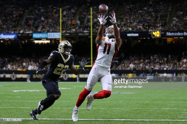 Larry Fitzgerald of the Arizona Cardinals attempts to catches the ball as Chauncey GardnerJohnson of the New Orleans Saints defends during the first...