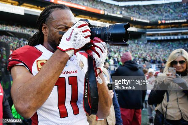 Larry Fitzgerald of the Arizona Cardinals borrows a camera and takes some pictures in the third quarter against the Seattle Seahawks at CenturyLink...