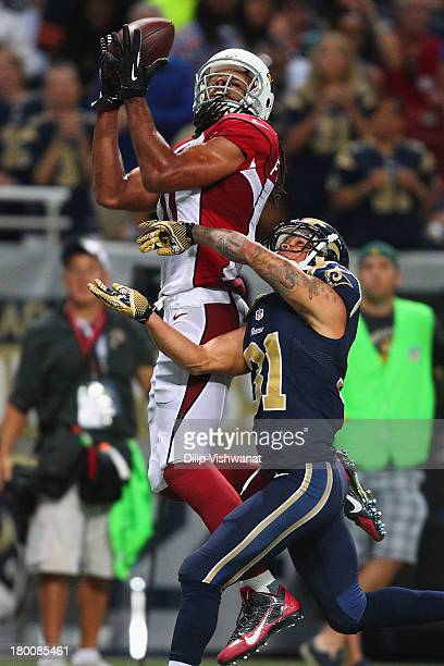 Larry Fitzgerald of the Arizona Cardinals catches a touchdown pass against Cortland Finnegan of the St Louis Rams at the Edward Jones Dome on...