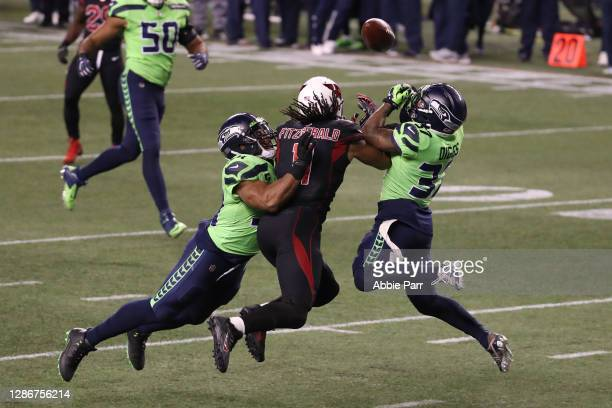 Larry Fitzgerald of the Arizona Cardinals has his pass broken up by Quandre Diggs and Bobby Wagner of the Seattle Seahawks in the fourth quarter at...