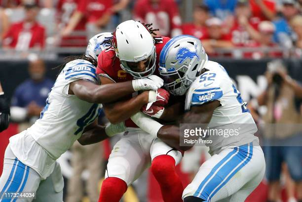 Larry Fitzgerald of the Arizona Cardinals is tackled by linebackers Jarrad Davis and Christian Jones of the Detroit Lions during the second half of...