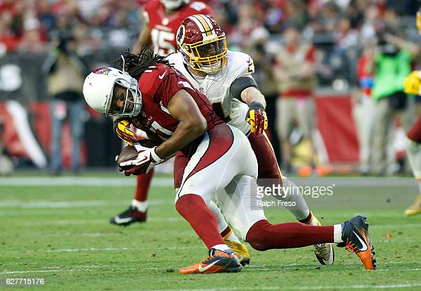 Larry Fitzgerald of the Arizona Cardinals is tackled by Mason Foster of the Washington Redskins after a catch during the third quarter of a game at...