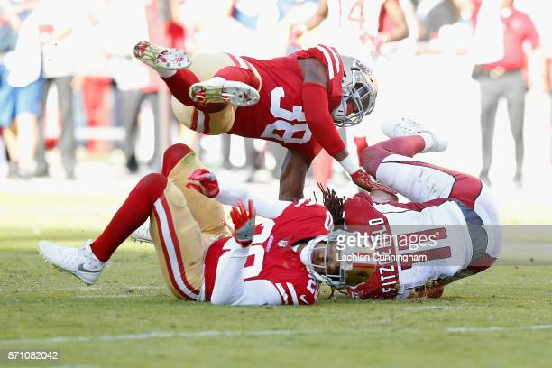 Larry Fitzgerald of the Arizona Cardinals makes a catch against Leon Hall of the San Francisco 49ers and Adrian Colbert of the San Francisco 49ers at...