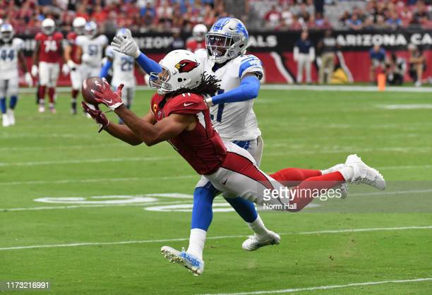 Larry Fitzgerald of the Arizona Cardinals makes a diving catch while being defended by Tracy Walker of the Detroit Lions during the fourth quarter at...