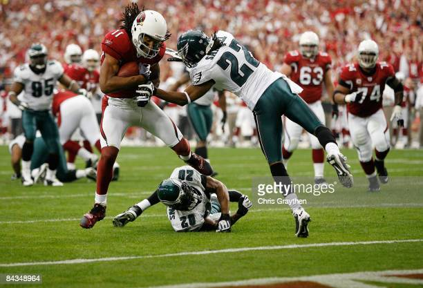 Larry Fitzgerald of the Arizona Cardinals runs past safety Brian Dawkins and cornerback Asante Samuel of the Philadelphia Eagles into the endzone for...