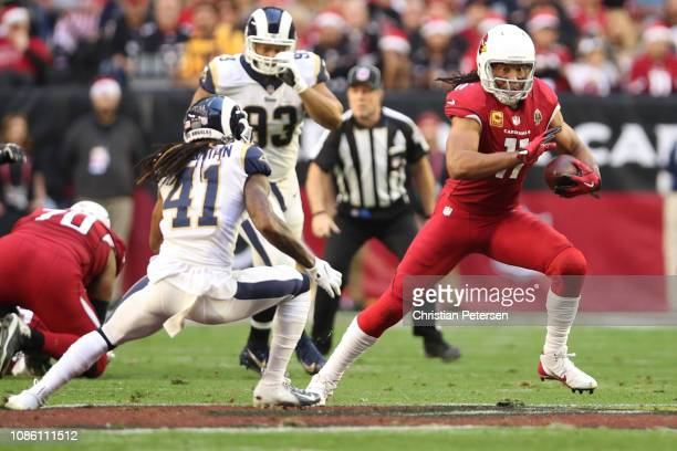 Larry Fitzgerald of the Arizona Cardinals runs with the ball in front of Marqui Christian of the Los Angeles Rams in the first half at State Farm...