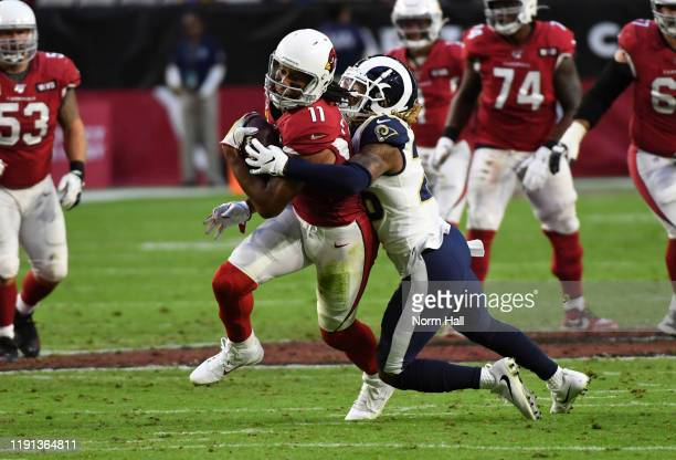 Larry Fitzgerald of the Arizona Cardinals runs with the ball while attempting to break a tackle by Marqui Christian of the Los Angeles Rams at State...
