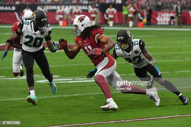 Larry Fitzgerald of the Arizona Cardinals runs with the football against Jalen Ramsey and Aaron Colvin of the Jacksonville Jaguars in the first half...
