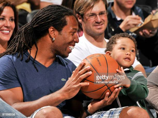 Larry Fitzgerald of the Phoenix Cardinals smiles holding the game ball with his son Devin as he sits courtside during the game between the Los...