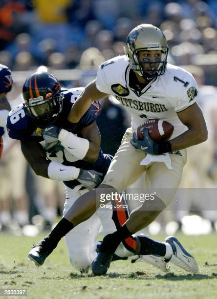Larry Fitzgerald of the Pittsburgh Panthers runs by Jermaine Hardy of the Virginia Cavaliers during the Continental Tire Bowl December 27, 2003 at...
