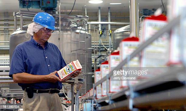 Larry Glodek <cq> production manager for Robinson Dairy inspects Horizon organic milk as it comes off the packaging line at Robinson's Denver plant...